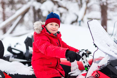 Cute boy in a red parka down jacket outdoors on beautiful winter snowy day on snowmobile Zdjęcie Seryjne - 155235463
