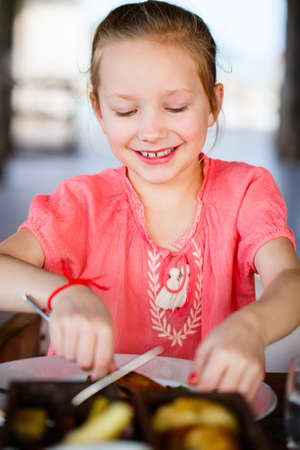 Casual portrait of adorable little girl enjoying meal at restaurant 写真素材 - 155326206