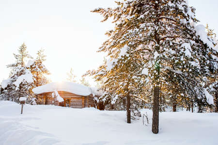 Beautiful winter landscape with wooden hut and snow covered trees in Finnish Lapland forest 写真素材 - 155235190