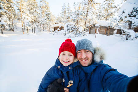 Family of father and his adorable little daughter outdoors on beautiful winter snowy day Zdjęcie Seryjne - 155235486