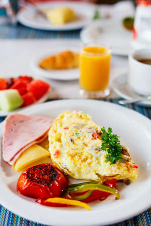 Delicious breakfast with omelet, ham and vegetables