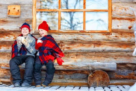 Kids outdoors on beautiful winter day drinking hot chocolate in front of log cabin vacation house Zdjęcie Seryjne