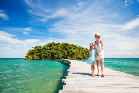 Family walking on wooden pathway leading to beautiful tropical island in Cambodia Zdjęcie Seryjne - 155235631