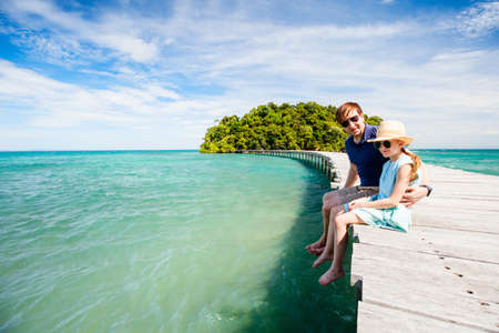 Family father and daughter enjoying tropical vacation relaxing on wooden pathway leading to beautiful tropical island in Cambodia Zdjęcie Seryjne - 155235626