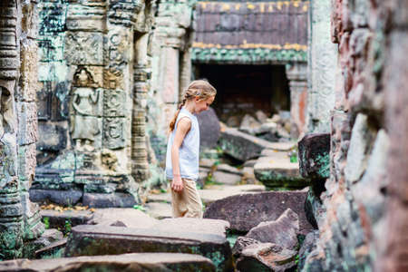 Little girl in ancient Angkor Wat temple in Siem Reap, Cambodia Zdjęcie Seryjne - 157630350