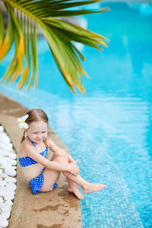 Portrait of adorable little girl wearing blue swimsuit in swimming pool