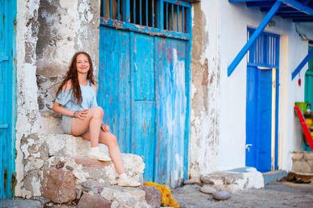 Adorable teenage girl enjoying visit to colorful fishing village of Klima on the island of Milos in Greece Zdjęcie Seryjne
