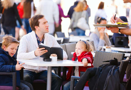 Young father and his two kids at outdoor cafe ordering food