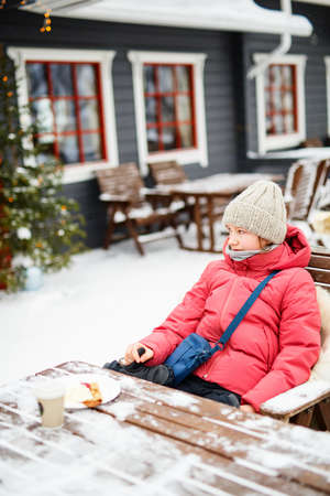 Adorable pre-teen girl wearing warm clothes in outdoor cafe on beautiful winter snowy day