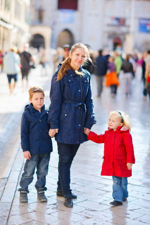 Young beautiful mother with her two kids in European city on sunny fall day Zdjęcie Seryjne