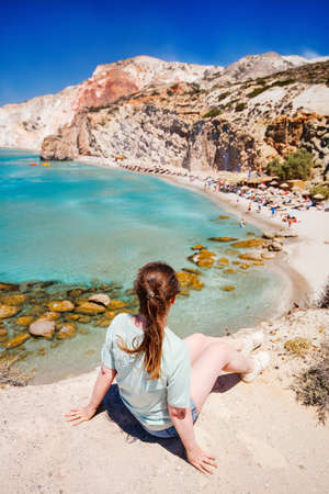 Young girl enjoying view of idyllic Fyriplaka beach on Greek island of Milos