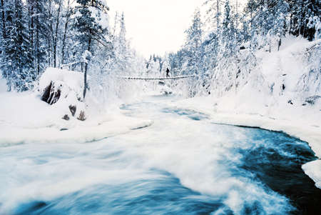 Stunning landscape of hanging bridge over river in snow covered forest in Oulanka National Park in Lapland Finland Zdjęcie Seryjne