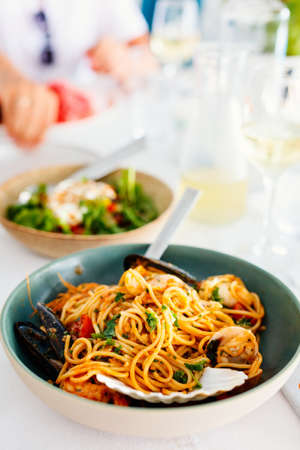 Delicious seafood spaghetti served with white wine for lunch or dinner in restaurant