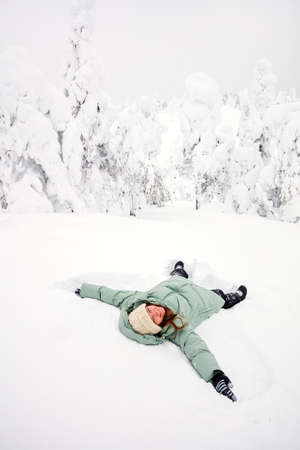 Happy girl lying down on snow and moving arms and legs up and down creating a snow angel figure Zdjęcie Seryjne