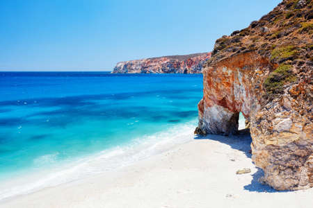 Idyllic beach surrounded by beautiful cliffs dotted with sea caves on Greek island of Milos Zdjęcie Seryjne