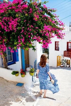 Young woman enjoying walk around old traditional Greek cycladic village of Plaka on Milos island
