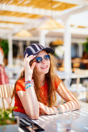 Cute teenage girl outdoors enjoying  time in outdoor cafe with family or friends on summer day