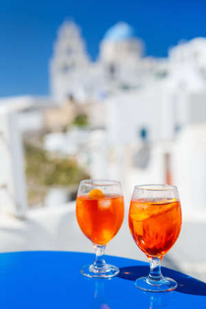 Two glasses of wine glasses on blue table with view of greek village with traditional white architecture and blue-domed church Zdjęcie Seryjne