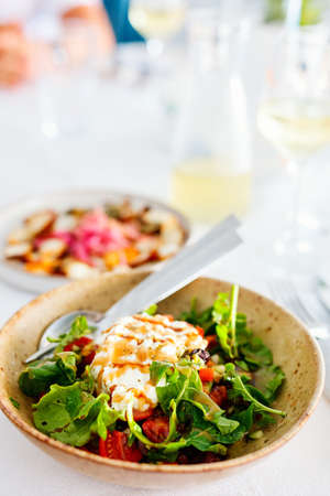 Delicious Santorini salad with fresh vegetables and Greek goat cheese served with white wine for lunch in restaurant Zdjęcie Seryjne