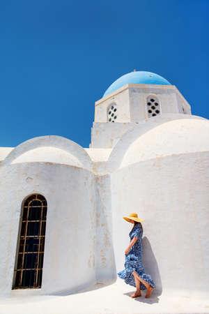 Beautiful young woman walking nearby blue domed church in Pyrgos village on Santorini island in Greece Zdjęcie Seryjne