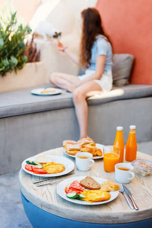 Omelet breakfast served outdoors on vacation house terrace where young girl playing with cat on background