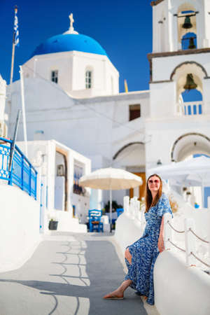 Beautiful young woman enjoying walking around  Pyrgos village on Santorini island in Greece with blue domed church and traditional whitewashed houses Zdjęcie Seryjne