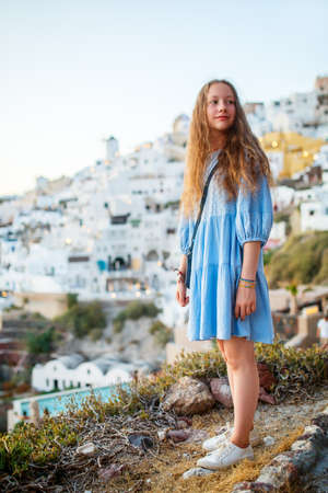 Cute pre-teen girl enjoying breathtaking sunset view of Oia village with traditional white architecture on Santorini island in Greece Zdjęcie Seryjne