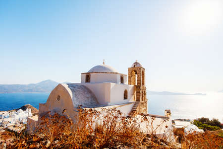 Breathtaking sunset view over traditional whitewashed Greek Orthodox church in Plaka village on Milos island