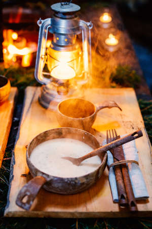 Bowl of delicious mushroom cream soup served in lappish hut next to open fire Zdjęcie Seryjne