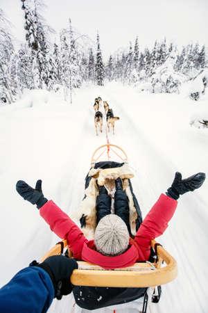 Family on husky safari enjoying ride on winter day in Lapland in Finland