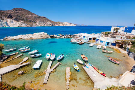 Traditional fishing village of Mandrakia with white houses and colorful doors, small harbor and fishing boats on Milos Island in Greece