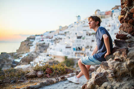 Teen boy enjoying sunset view of Oia village with traditional white architecture on Santorini island in Greece