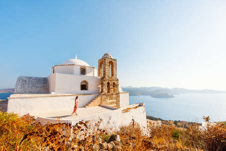 Young girl enjoying breathtaking sunset view from atop of traditional whitewashed Greek Orthodox church in Plaka village on Milos island