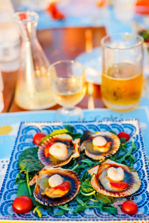 Delicious grilled scallops served on shells with fresh vegetables and white wine for lunch or dinner in restaurant