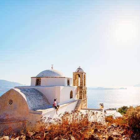 Young man enjoying breathtaking sunset view from atop of traditional whitewashed Greek Orthodox church in Plaka village on Milos island