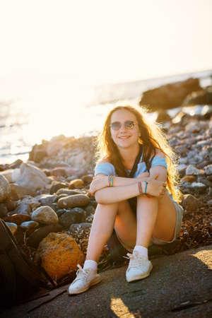 Adorable teenage girl outdoors enjoying sunset at beach on summer day
