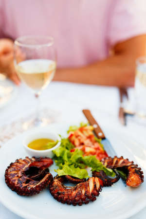 Delicious grilled octopus served with fresh vegetables and white wine for lunch or dinner in restaurant Zdjęcie Seryjne