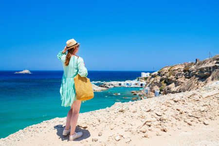 Back view of young woman enjoying view of Mediterranean sea and traditional fishing village of Mandrakia on Milos Island in Greece
