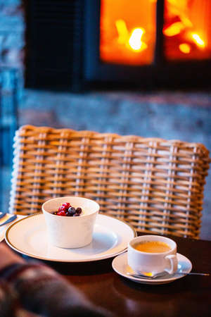 Fresh coffee and desert served in restaurant with fireplace on background 免版税图像