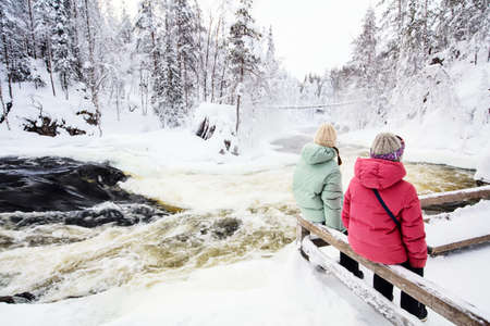 Back view of mother and daughter enjoying breathtaking view of winter landscape in Oulanka National Park in Lapland Finland