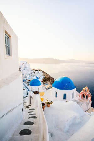 Blue domed church in Oia overlooking spectacular caldera surrounding beautiful island of Santorini in Greece 免版税图像