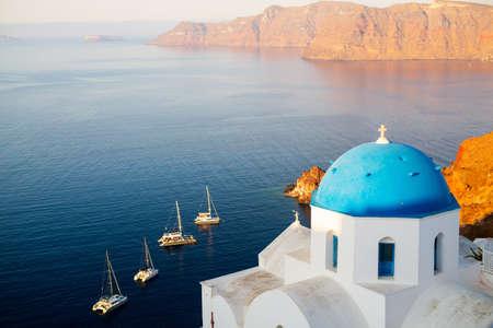 Blue domed church in Oia overlooking spectacular Aegean sea and caldera surrounding beautiful island of Santorini in Greece 免版税图像