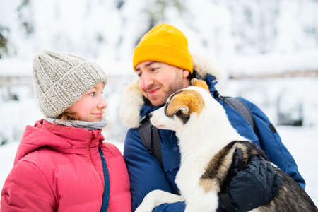 Family of father and his adorable pre-teen daughter cuddling with husky puppy outdoors on winter day in Lapland Finland