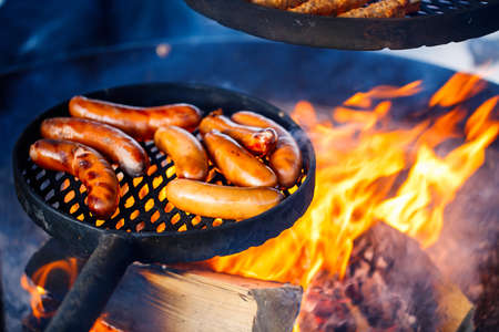 Sausages grilled over open fire outdoors 免版税图像
