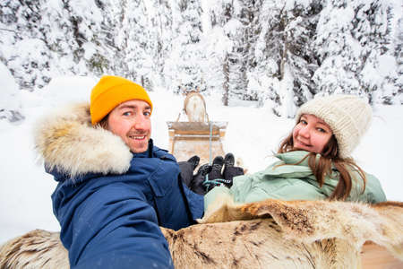 Happy couple on reindeer safari in winter forest in Lapland Finland 免版税图像