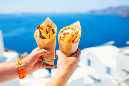 Greek gyros wrapped in pita bread photographed against traditional greek town with white houses