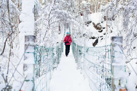 Cute pre-teen girl crossing over hanging bridge in  winter forest in Oulanka National Park in Lapland Finland