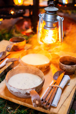 Delicious mushroom cream soup served in wooden bowls in lappish hut next to open fire 免版税图像