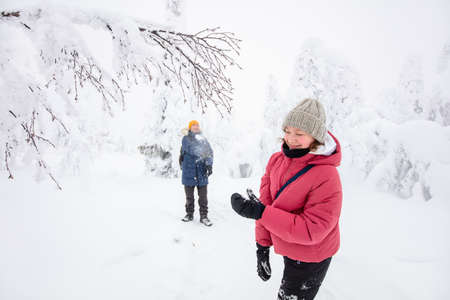 Family of father and daughter having fun playing in snow covered winter forest in Lapland Finland 免版税图像