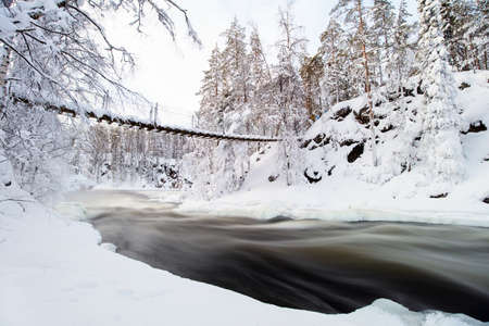 Stunning landscape of hanging bridge over river in snow covered forest in Oulanka National Park in Lapland Finland 免版税图像